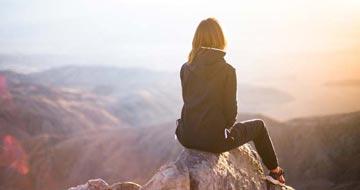 Kvinde der sidder på en bjergtop
