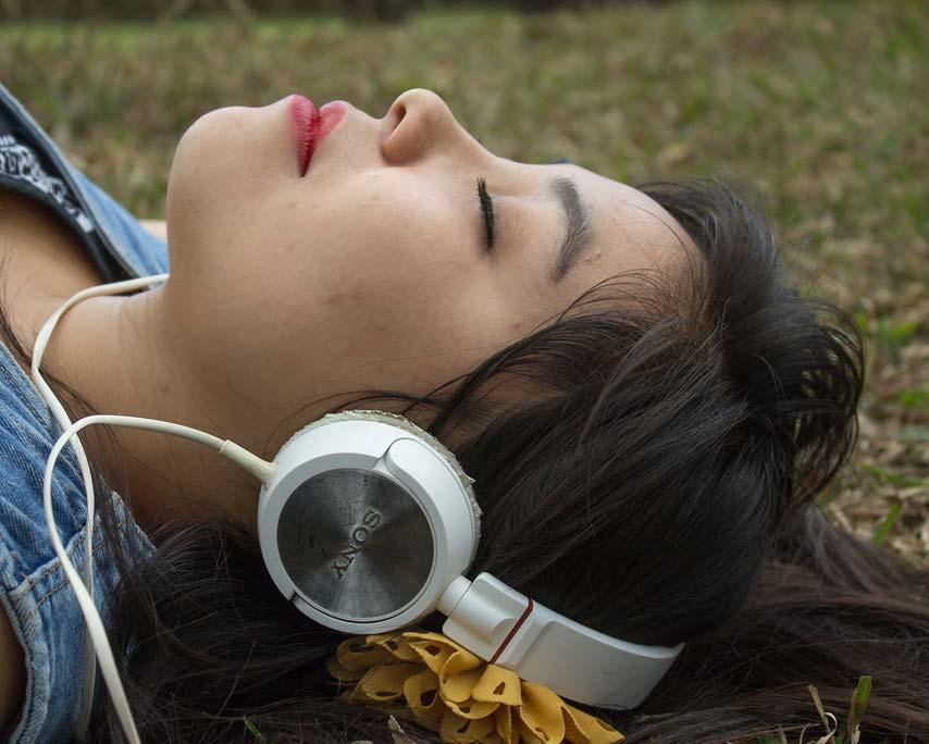 """UUng kvinde med høretelefoner på lytter til ViaVitas hypnose """"Ro, afslapning og velvære"""""""